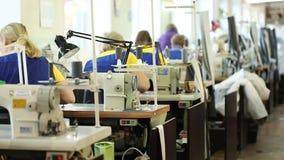 Vrouw die bij een naaimachine, Industriële grootte textielfabriek, arbeiders op de productielijn, industrieel binnenland werken stock footage