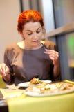 Vrouw die bij een restaurant eten stock foto's