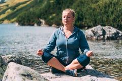 Vrouw die bij het meer mediteren Royalty-vrije Stock Fotografie