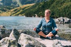 Vrouw die bij het meer mediteren Stock Foto