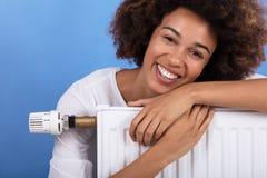 Vrouw die bij het Verwarmen van Radiator leunen stock afbeeldingen