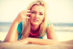 Vrouw die bij het zandige strand ontspannen tijdens de zomer liggen Stock Fotografie