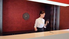 Vrouw die bij hotelontvangst op de telefoon spreken stock video