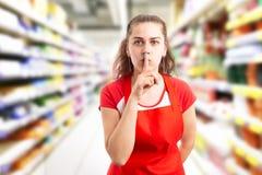 Vrouw die bij hypermarket werken die gebaar maken doen zwijgen royalty-vrije stock foto