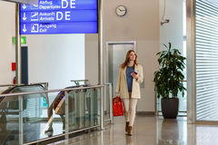 Vrouw die bij internationale luchthaven op vlucht wachten Royalty-vrije Stock Afbeeldingen