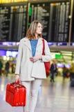 Vrouw die bij internationale luchthaven op vlucht wachten Stock Afbeelding