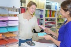 Vrouw die bij kantoorbehoeftenteller worden gediend royalty-vrije stock foto