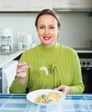 Vrouw die bij keuken eet Stock Afbeeldingen