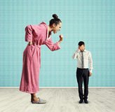 Vrouw die bij kleine vermoeide echtgenoot gillen Stock Foto