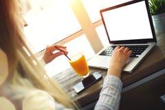 Vrouw die bij laptop in de comfortabele in koffiezitting dichtbij een groot venster bij een lijst met een glas werken van of Royalty-vrije Stock Foto