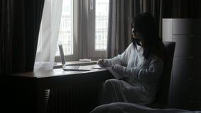 Vrouw die bij laptop schrijven stock video