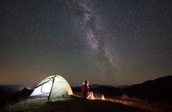 Vrouw die bij nacht rusten die in bergen onder sterrige hemel kamperen royalty-vrije stock afbeeldingen