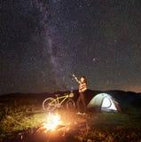 Vrouw die bij nacht rusten die dichtbij kampvuur, toeristentent, fiets onder het hoogtepunt van de avondhemel van sterren kampere stock fotografie