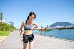 Vrouw die bij ochtend lopen en het verslag controleren op slim horloge stock foto's