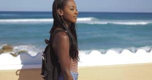 Vrouw die bij omheining bij oceaan lopen stock video