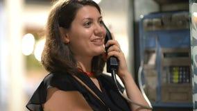 Vrouw die bij Openbare Telefoon spreken stock footage