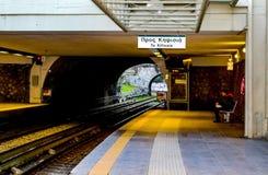 Vrouw die bij openlucht behandelde metro post in vroege ochtend met trein het naderbij komen wachten royalty-vrije stock afbeeldingen