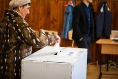 Vrouw die bij opiniepeilingspost stemmen royalty-vrije stock foto's