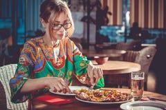 Vrouw die bij restaurant eten Stock Fotografie