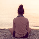 Vrouw die bij rustige strandzonsondergang mediteren Stock Afbeeldingen