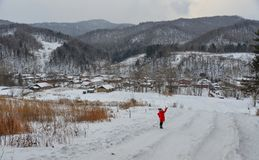 Vrouw die bij sneeuwdorp lopen in China stock afbeelding