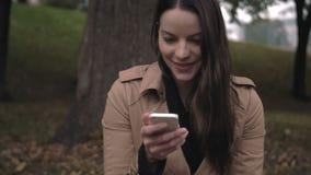 Vrouw die bij tekst lachen die zij op haar cellulair apparaat heeft ontvangen stock footage