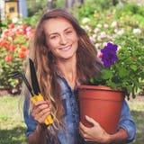 Vrouw die bij tuin werken stock afbeelding
