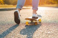 Vrouw die bij zonsopgang met een skateboard rijden Benen op het skateboard, bewegingen aan royalty-vrije stock foto