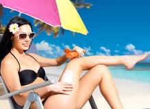 Vrouw die in bikini de room van het zonblok op lichaam toepassen Royalty-vrije Stock Foto