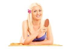 Vrouw die in bikini een chocoladeroomijs op een stok eten Royalty-vrije Stock Fotografie
