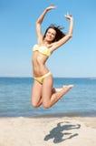 Vrouw die in bikini op het strand springen Stock Afbeeldingen