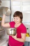 Vrouw die binnen aan pan van ijskast kijkt Royalty-vrije Stock Foto