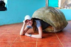 Vrouw die binnen lege reuze de schildpadshell van de Galapagos bij s liggen stock afbeeldingen