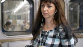 Vrouw die binnen metro aan muziek met telefoon luisteren stock foto's
