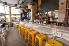 Vrouw die binnen moderne koffie met barteller en vele flessen met alcohol dineren Royalty-vrije Stock Foto's