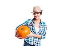 Vrouw die in blauw gecontroleerd overhemd, hoed oranje pompoen houden stock afbeelding