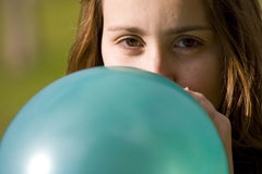 Vrouw die blauwe ballon opblaast Stock Foto's