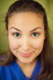 Vrouw die blauwe blouse met kwaadwillige glimlach draagt Royalty-vrije Stock Foto's