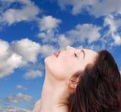 Vrouw die blauwe hemel ontspant stock afbeelding