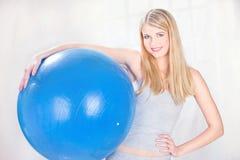 Vrouw die blauwe pilatesbal houden Stock Foto's