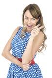Vrouw die Blauwe Polka Dot Dress Pointing Laughing dragen Stock Afbeeldingen