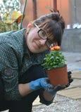 Vrouw die bloemen plant Stock Fotografie