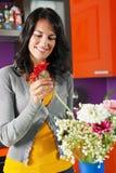 Vrouw die bloemen in pot schikt stock afbeelding