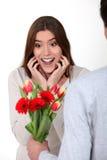 Vrouw die bloemen van haar vriend ontvangt Stock Fotografie