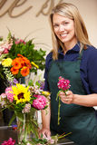 Vrouw die in bloemist werkt Stock Foto's