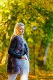 Vrouw die bont lang vest dragen tijdens de herfst stock fotografie