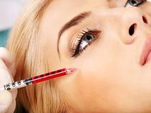 Vrouw die botox injecties geeft. Stock Foto's