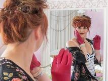 Vrouw die in boudoir in spiegel kijken gesteld stock foto