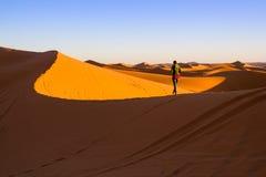Vrouw die bovenop een zandduin lopen stock afbeelding