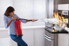 Vrouw die Brandblusapparaat gebruiken om Brand van Oven te doven stock foto's